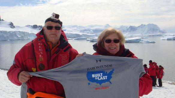 Two people holding Baron t-shirt in Antarctica. Activating element opens larger version of image.